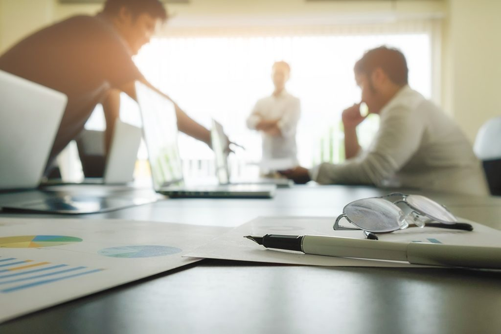 Profissionais em reunião com planilhas, conversando, atentos e pensativos.